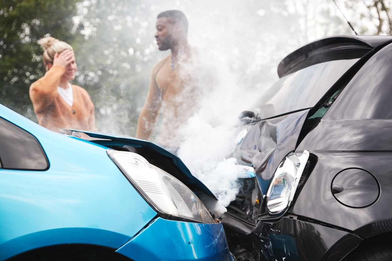 Photograph of a man & woman standing near their cars after having a car accident. One cars hood has damage after crashing.
