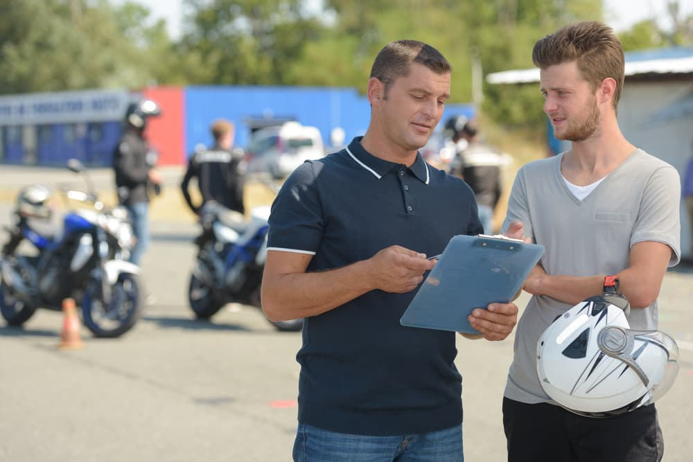 motorcycle driving instructor talking to candidate